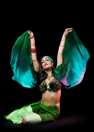 young beautiful oriental woman with a veil dancing over a dark background photo