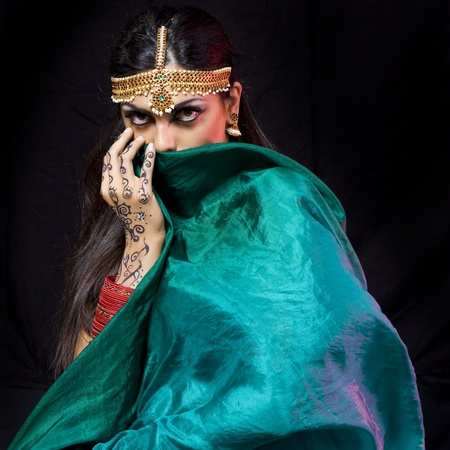 young beautiful oriental style woman covering herself with a green veil photo