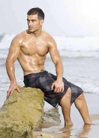pectoral muscle: sexy caucasian fit man posing in a beach