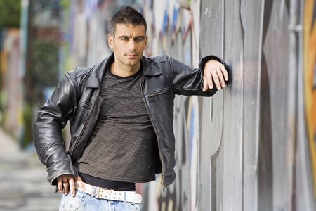 tough man: adult handsome man posing outdoors in a graffiti wall background Stock Photo