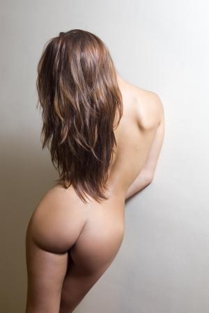 attractive young woman posing against the wall in an artistic nude Stock Photo