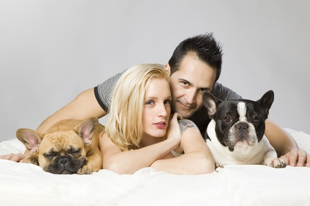 young sexy man and a woman with two funny french bulldogs