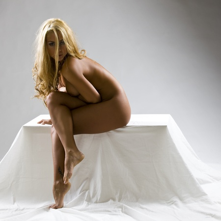 young beautiful woman posing nude in a photo shooting in the studio