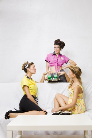 a group of pin-up girls drinking something in a bar photo