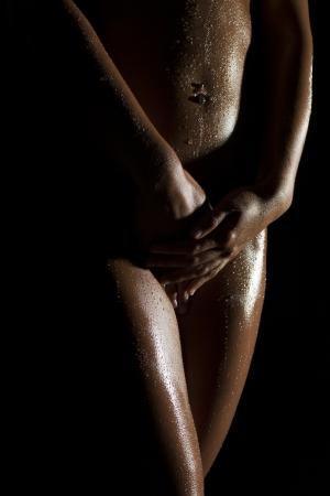 femme se deshabille: formes du corps f�minin sexy et des courbes sur un fond sombre
