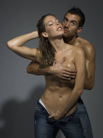 adult sex: a man and a woman foreplaying in grey blackground