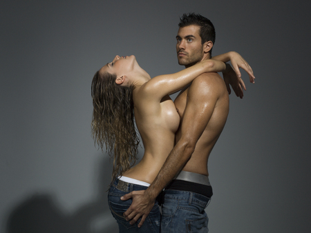 female breast: a man and a woman foreplaying in grey blackground