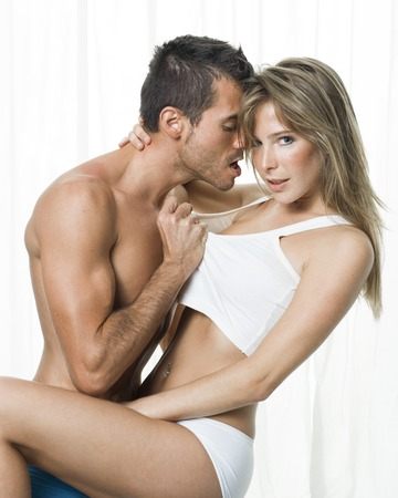 adult sex: a man and a woman foreplaying in white background Stock Photo