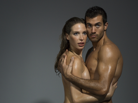 erotic breast: man and woman with nude torso foreplaying in grey background Stock Photo