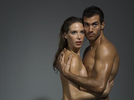 nudo integrale: uomo e donna con nudo foreplaying il torso in fondo grigio