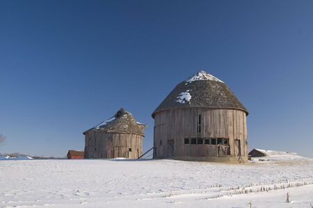 barns winter: Two round barns in winter setting on farm