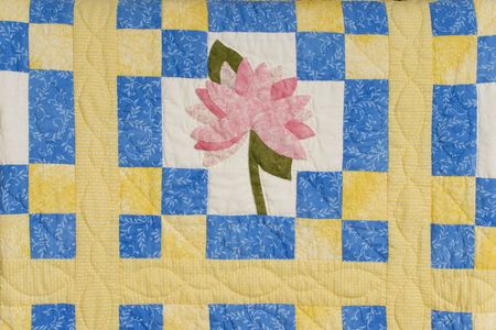 A colorful blue and yellow quilt with pink flower.