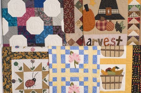 A grouping of various quilts on wall hanging rack.