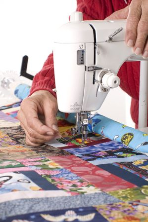 A woman quilter is pulling new thread through the sewing machine to begin quilting.
