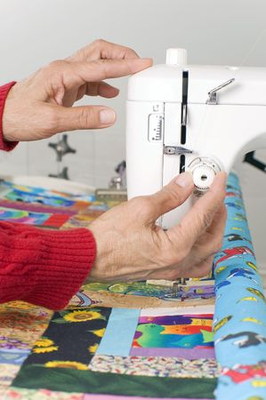 prior: A quilter sets the tension dial prior to sewing a quilt.