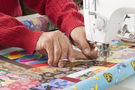 A woman quilter is cutting excess thread on a sewing machine. photo
