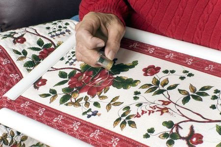A woman hand quilts a new quilt using a plastic frame.