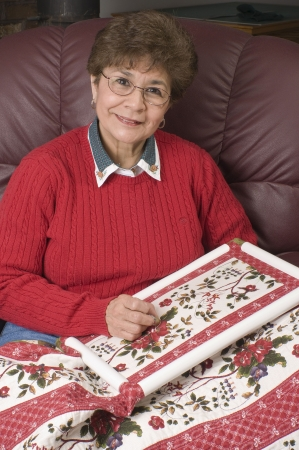 A woman smiles while hand quilting a new floral quilt. Stock Photo
