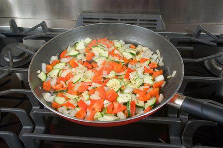 sautee: Un medoly di veggies fresche sono sauteed in una padella per essere utilizzato in una pizza vegetariana. Archivio Fotografico