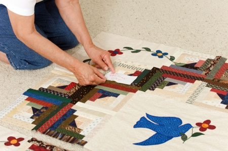 prior: A quilter pins a paper label on a section prior to final assembly.