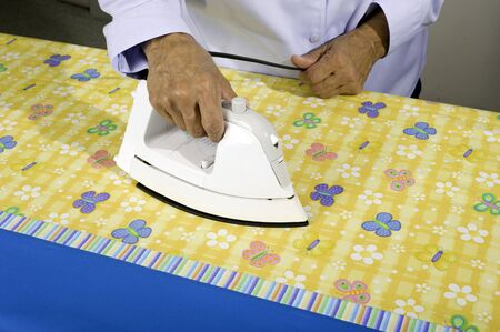 pillow case: A woman irons colorful fabric to be used in making a pillow case.