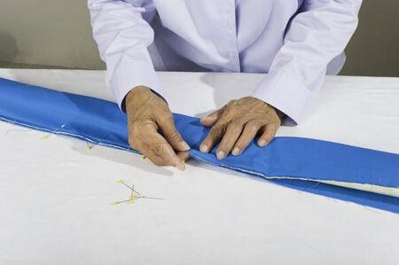 pillow case: A woman pins fabric to make a tubular pillow case. Stock Photo