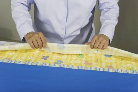 pillow case: A woman rolling fabric to create a tubular pillow case. Stock Photo