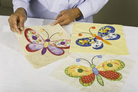 A quilter lays out three squares of colorful butterfly patterns to be used in a quilt.