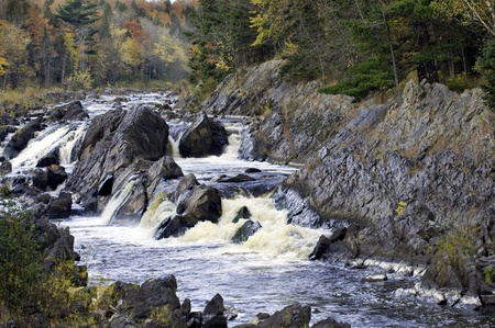 Water rushes over jagged boulders and outcrops along the St. Louis river,Minnesota.