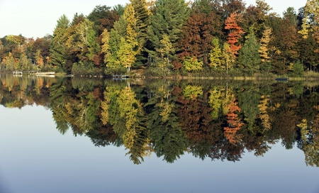 Calm lake waters provide a beautiful reflection of fall colors.