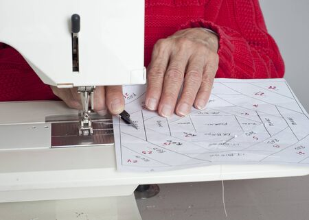 off cuts: A quilter cuts off excess material from a quilted square of fabric