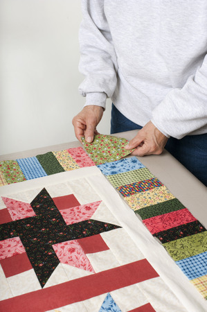 A quilter arranges a square of fabric for the cornerstone of a quilt top border