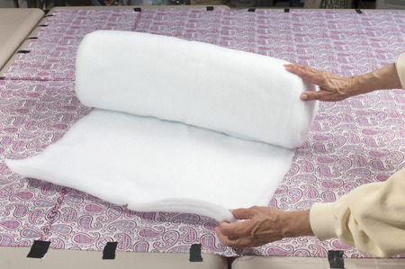 white backing: Preparing to unroll polyester batting for use in a quilt.