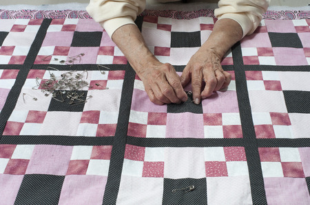 Pinning quilt top to the back in preparation for quilting.
