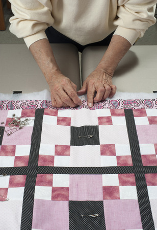 pinning: Pinning quilt top to the back in preparation for quilting.
