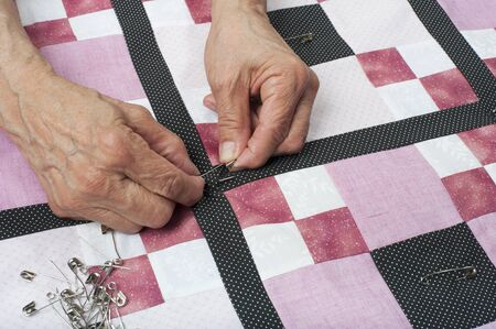 pinning: Quilter pinning quilt top to backing.