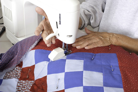 A female quilter lifting the walking foot lever after completing the grid pattern on a patriotic quilt.