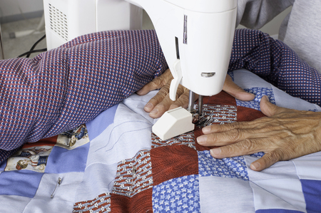 A woman machine quiltingsewing three layers to create a patriotic quilt.