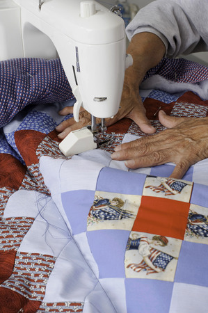 white backing: A quilter quiltingsewing a grid pattern to complete a patriotic quilt. Stock Photo