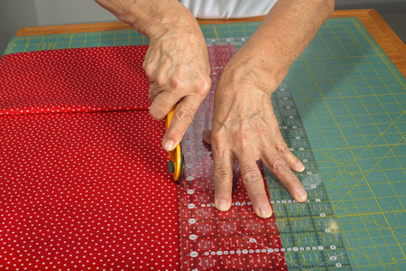 A woman cuts colorful red fabric with a rotary cutter for use in a new quilt.