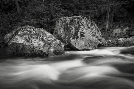 Two large granite boulders sit along side a rushing stream in eastern Tennessee.