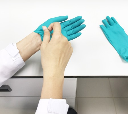 Scientists are removing green synthetic rubber gloves through laboratory sterilization.