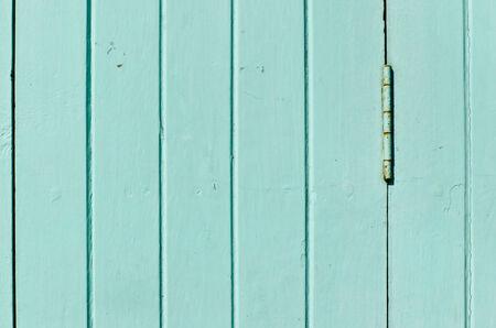 Rusty hinge on light blue door Stock Photo