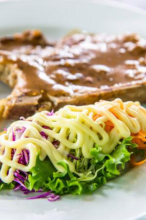 Closeup image of steak dish with salad
