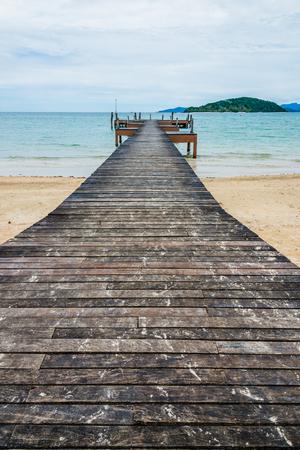 Image of long hardwood bridge over the sea in Thailand