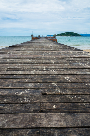 Image of old and long hardwood bridge on the sea in Thailand