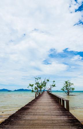 Image of old hardwood bridge on the beach in Thailand
