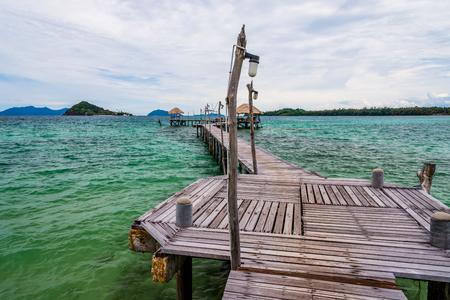 Image of old hardwood bridge on the sea in Thailand