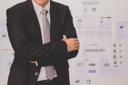 front view: Male model in a suit posing on office background
