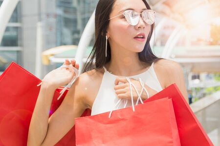 happy young couple with shopping bags walking in mall Stock Photo - 81035226